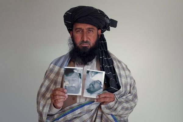 Kareem Khan with picture of his son, killed by a drone. Credit: Noor Behram/Reprieve
