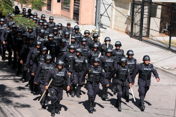 A column of Honduran police in riot gear