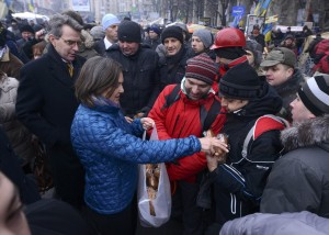 U.S. Assistant Secretary of State for European and Eurasian Affairs Nuland distributes bread to protesters next to U.S. Ambassador Pyatt at Independence square in Kiev